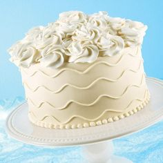This easily elegant cake design is created with generous rosettes on top. Encircled by icing swirls, this buttercream cake is ideal for showers, celebrations and garden parties.