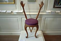 The Hands (or Arms) Chair suggested by Salvador Dali in 1936. Carved walnut frame with purple leather-covered seat. The working drawing was made by Edward James, and the chair was produced specifically for James' residence, West Dean. http://www.chairblog.eu/2010/03/10/hands-chair-by-salvador-dali/