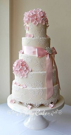 """Lace and Hydrangeas Wedding Cake A very pretty 5 tier cake for the lovely Sophia and Raffaele. The cake was designed to match the wedding invitations, dress and flowers. It is sitting on a hessian covered separator and decorated with pieces of sugar lace, with a wrap of scalloped lace draping around the base and embellished with piped icing """"pearls"""" Finished with arrangements of baby pink sugar hydrangeas, a satin ribbon and pretty brooch."""