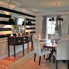 Mix of antique and modern, large black painted stripes, stunning sideboard, black shades on lamps and chandelier, white linen chairs. (I really like this room)