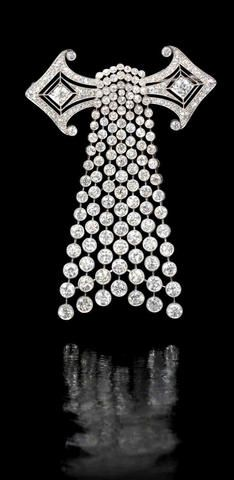 An art deco diamond brooch, circa 1920 The pierced geometric plaque issuing an articulated cascade of graduated diamonds, millegrain-set throughout with old brilliant-cut diamonds, mounted in platinum, diamonds approximately 15.20 carats total, French assay marks, length 7.8cm
