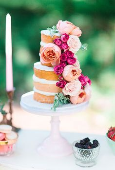 A two-tiered naked wedding cake decorated with pink peonies and roses