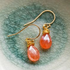 Shimmering orange carnelian gemstones on 14 karat gold earrings.