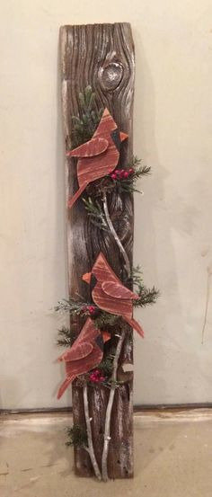Wooden red birds paper mache vines and leaves on fence boarding.