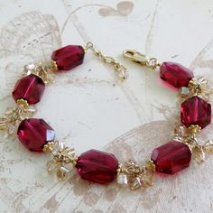 Sophisticated artisan style ruby Swarovski crystal bracelet is handmade with cool red hued modern cut Swarovski crystals. Accented with yellow champagne Swarovski dangles. Set in 14k gold filled findings for a lasting finish. A gorgeous gift for a lucky woman born in July since ruby is her
