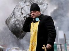 A priest holds a cross and shield during clashes between anti-government protesters and riot police in central Kiev, Ukraine, on February (Sergey Gapon/AFP/Getty Images Orthodox Priest, Orthodox Christianity, Catholic Memes, Powerful Pictures, Frederique, Riot Police, Lord Is My Strength, Fight For Freedom, Fotografia