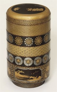 A jubako [food container)  Edo Period (18th Century)  The cylindrical five-tiered box and cover decorated in gold and silver hiramaki-e and nashiji on a black ground with bands of geometric design, water wheels, fans and three panels depicting landscapes between peonies and scrolling foliage, the cover with karako, red lacquer interior 30.5cm. high