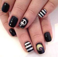Black and white A Nightmare before Christmas themed nail art. Celebrate Halloween wit this classic tale of creepiness on your own nails. Have fun in recreating the ghastly character on your nails accompanies by black and white stripe designs.