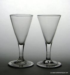 Pair of Georgian Folded Foot Gin Glasses c1750 George II Origin : England Colour : Clear Bowl : Drawn conical Stem : Plain Feet : Conical, folded Pontil : Snapped Glass Type : Lead Size : 4 3/8 inches tall with a 2 1/8 inch bowl and 2 ¼ inch folded feet Weight : 132 grams http://scottishantiques.com/Georgian-drinking-glasses/antique-gin-glass?product_id=6016#.V7GxbVsrJeh