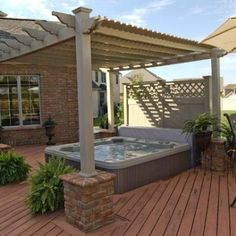Beige colored Vinyl Pergola over a recessed Hot Tub with Brick Pillars and Privacy Fence.  Want to attain more privacy in your hot tub?  This partially recessed hot tub allows for easy access.  Privacy Fence was built on top of deck which provided access to mechanicals on tub.  The brick pillars were installed to match brick on the home.  Exquisite setting.  Project completed in Washington Court House, Ohio, Columbus, Ohio