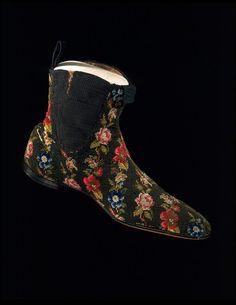 Men's wool-embroidered canvas boots with elastic gussets, British, 1845-1865. Half-boots (ankle boots) were popular for men from the 1830s right up to the Depression in the 1930s. Most were made of leather, though softer materials were popular for informal wear. Women often embroidered the uppers of boots and slippers for their families as well as for themselves. The elastic-sided boot was patented in 1837. The elasticated side gussets eliminated the need for laces and button fastenings.