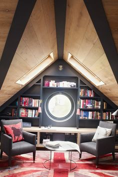 The porthole window of this attic bedroom in west London is beautifully framed with stylish black bookshelves; a clever use of storage in an...