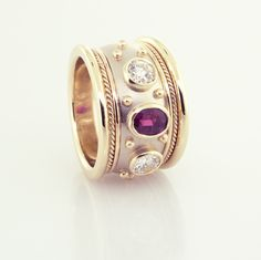 Ruby and Diamond Cigar band set in 14KT white and yellow gold, .90ct. ruby and two .33ct. round brilliant shape diamonds
