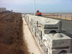 CPM's Redi-Rock walling being installed in Rhyl to give a look of natural walling and protect against weather conditions Precast Concrete, Concrete Blocks, Drainage Pipe, Free Standing Wall, Modular Walls, Stone Masonry, Cost Saving, Landscape Walls, Retaining Walls