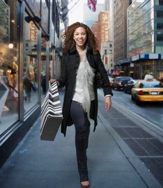 Woman carrying shopping bags down urban street