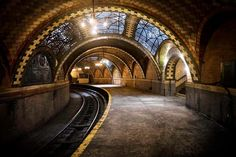"NYC's hidden subway station. Under the streets of NYC lies a forgotten and beautiful secret. This amazingly preserved station, unused since the 1940's, features arched tile ceilings and brass fixtures. ""City Hall Station"" was closed down due to compatibility problems with newer subway cars and general lack of use. Ride through the station on the Number 6 train as it makes its slow turnaround through the old station; you can't get out, but you can see a largely untouched relic of NY's Golden…"