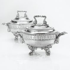 A Pair of Regency Silver Circular Sauce Tureens, Covers and Liners, Paul Storr, London, 1819 the bodies partly gadrooned and applied with band of stiff leaves and anthemia, engraved on both sides with contemporary arms and supporters, the reeded loop handles springing from lion heads and centered by shells, raised on four paw feet headed by classical foliage, the conforming covers with loop finails, engraved with hound and unicorn crests, removable liners with matching crests