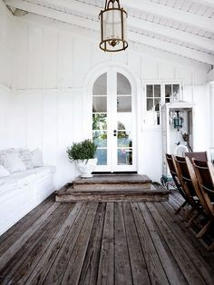 A doorway from a covered patio into a home. Everything about this semi-outdoor space seems lovely to me, the arched glass door, the weathered deck flooring, the built in seating.