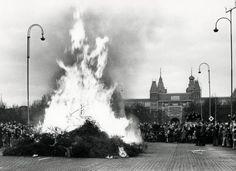 Vlakbij het Rijksmuseum zijn mensen komen kijken naar de kerstboomverbranding. Enkele politieagenten kijken toe. Amsterdam, [1960].