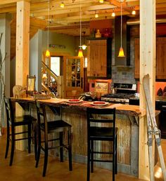 The corrugated metal on this bar add a rustic feel to a lake cabin. Kitchen by Lands End Development. | Stylish Western Home Decorating