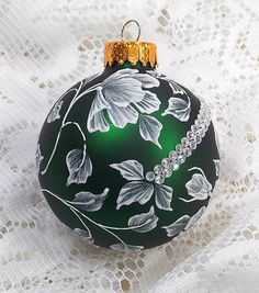 Emerald Green glass ornament with White 3D texture painted MUD design with iridescent rhinestone bling. Each ornament I create is a one-of-a-kind. The texture medium and paint brush I use to paint the ornaments were both created to my specifications. My signature M is located on the bottom of the ornament. Gift boxed. Measures 3 x 3 Ornament weight is 2 ounces.
