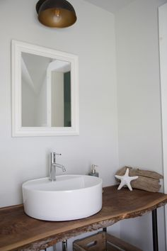 Rustic wood bathroom vanity with white cylinder sink