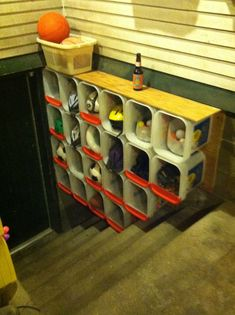 Picture of Kitty Litter Bucket Cubbies lining the staircase. Individual catchalls for each member of the family to reclaim their stuff they left downstairs on their way back up.