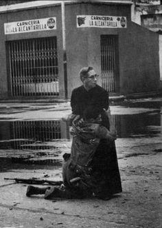 Un soldado herido de muerte por un francotirador abraza al capellan Luis Padillo en la base naval de Puerto Cabello,Venezuelafoto Hector Rondon,50 mejores fotos de la historia (premiadas)
