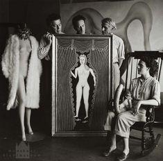 """Hermann Landshoff – Leonora Carrington vor dem Gemälde """"Akt am Fenster"""" des Malers Morris Hirshfield sitzend, dahinter stehend André Breton, Marcel Duchamp und Max Ernst (v.l.), New York"""