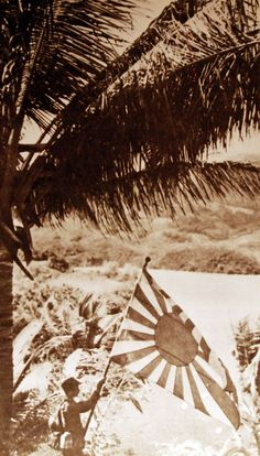 Japanese soldier holding Japanese flag following invasion and take over of Mindoro, Philippines, 1942.