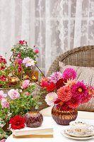 Sommerliche Terrasse mit Korbstuhl & Dahlienstrauss auf Tisch