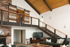 Stairs, stair rails, rustic modern living room, barn doors, contemporary gray sofa. House Redesign by REIER Construction