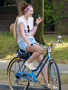 ELIZABETH OLSEN FASHION STYLE BLOG FILMING A SCENE FOR NEW MOVIE VERY GOOD GIRLS PRINT TSHIRT TEE DENIM CUT OFF SHORTS STRAW FLOPPY HAT RINGS BRACELETS AMERICAN FLAG SCRF HEAD WRAP BIKE BICYCLE SNEAKERS