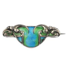 An early 20th century silver enamel brooch, the blue and green enamel panel to the scrolling and geometric sides. Hallmarks for Birmingham | JV