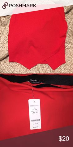 Bebe Red asymmetrical spandex skirt Nylon spandex red Bebe skirt. Pointed pleat in the front. Straight horizontal hem in the back. Black elastic band inside waist. Size M but runs big if you're looking for a fitted/tight skirt. Never worn!! bebe Skirts Mini