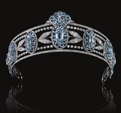 Belle Epoque Aquamarine Tiara, Circa 1910 - Designed as a series of graduated oval aquamarine clusters set with oval- and hexagonal-shaped aquamarines, interspersed with sprays of diamond myrtle leaves, within millegrain borders of circular-, single- and rose-cut diamonds, inner circumference approximately 370mm, fitted red leather and gilt tooled case.