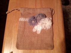 Burlap dollar dance bag embellished with white and shades of gray shabby flowers and beaded feathers.