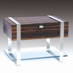 Estrella Table designed by Stanley Jay Friedman.     The Estrella, a small occasional / night table, defines highly skilled craftsmanship. It is made with a box drawer of full finished Macassar Ebony on top and a thick plate glass shelf on bottom, uniquely tied together with polished stainless steel straps. The Estrella Table is available in many of Brueton's exotic veneers and opaque finishes and can also be optioned with a top glass shelf and drawer unit on the bottom.