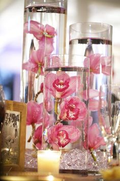 Pink Orchids submerged in cylinder vases of varying heights - so pretty! Not sure how it works in terms of keeping them fresh but they look beautiful. Would be interesting to see if you can put a floating candle on time. I really like the simplicity of it and seems like it could maximize the floral budget...