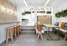 Il pavimento in parquet di rovere prosegue anche nella seconda sala di Vino Veritas, ad Oslo. Qui trova spazio anche un bancone a parete con sgabelli alti in legno per degustazioni di vino informali. L'interior è curato dallo studio Masquespacio