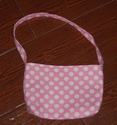 This little purse is the perfect size for a toddler girl.    Purse measures 8 inches long by 5.5 inches deep with an inch width. The strap is 7 inches long from top of purse to end of strap. Fabric is 100% cotton  Machine washable  Made in a pet free/smoke free environment    There is a layer of interfacing sandwiched between the outer and inner fabrics to provide a little stability. I started out making these purses for my one year old, she loves purses. I just kept making them because...