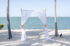Altar in white and pink/white roses arrangements in the sandy beach for the ceremony by the clear water view.