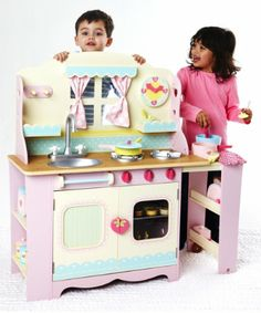 Educational Toys and Games. Spring/Summer 2014. ELC Wooden Cottage Kitchen. Lovely country-style wooden play kitchen featuring a window with curtains and a play clock too. #Kids #Toys #Fun