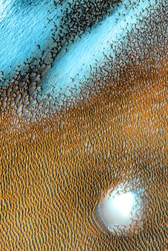 A sea of dark dunes, sculpted by the wind into long lines, surrounds the northern polar cap. The false-color image records areas with cooler temperatures in bluer tints, while warmer features safe depicted in yellows and oranges. | NASA