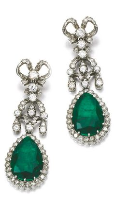 PAIR OF EMERALD AND DIAMOND EARRINGS, 1950S The surmounts of ribbon design, set with circular- and single-cut diamonds, suspending pear-shaped emeralds, post fittings.