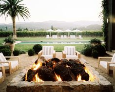 Outdoor fire pit of Wine Country home with striped lounge chairs and palm trees