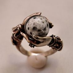 This celestial ring features a full moon crafted from hand-blown glass. The Oracle's hands wear a tiny white topaz ring. As you can imagine, they can be rather expensive – but we're giving one away for free! It only takes a few seconds of your time. Winner receives an oxidized brass ring, available in their choice of ring size from US 4 to US 12. Enter to win here!
