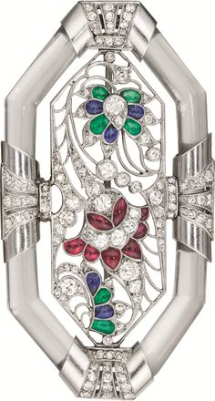 An Art Deco Diamond, Crystal, Platinum and Multi-Gem Brooch, attributed to Janesich. Of an elongated octagonal outline, centring upon an openwork mounting of foliate design set with circular-cut diamonds and buff top cabochon rubies, emeralds and sapphires, to the oblong rock crystal border enhanced with platinum terminals decorated with circular-cut diamonds, mounted in platinum. #ArtDeco #Janesich #brooch