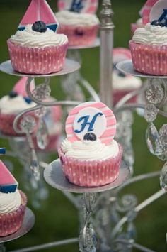 pink and navy blue nautical themed baby shower pink cupcakes with personalized toppers on pedestal stand