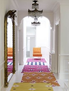 Layer ikat print rugs to give a pop of color to an all-white hallway